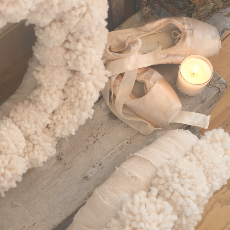 Wooly ivory handmade pom pom wreaths with pale pink ballet slippers and candlelight for Christmas - Hello Lovely Studio. #christmasdecor #serenechristmas #pompomwreath #hellolovelystudio