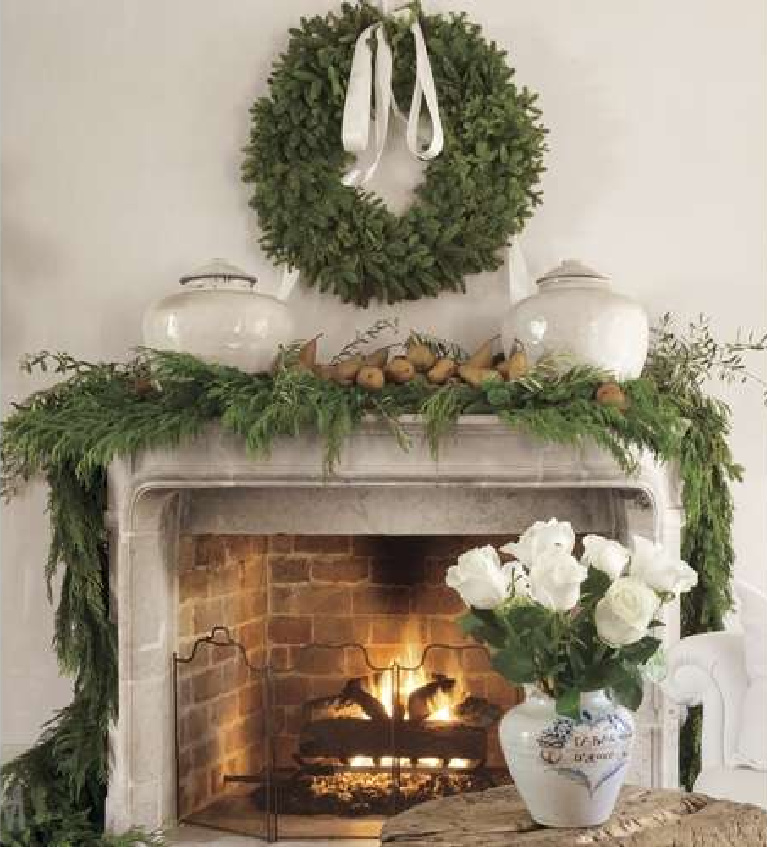 Breathtaking with natural greenery, antique French pots, and pears, a stone fireplace is decorated for the holidays in Pamela Pierce's Houston home. #christmasfireplace #christmasmantel #frenchcountry #whitechristmas #christmasdecor #pamelapierce #milieumag