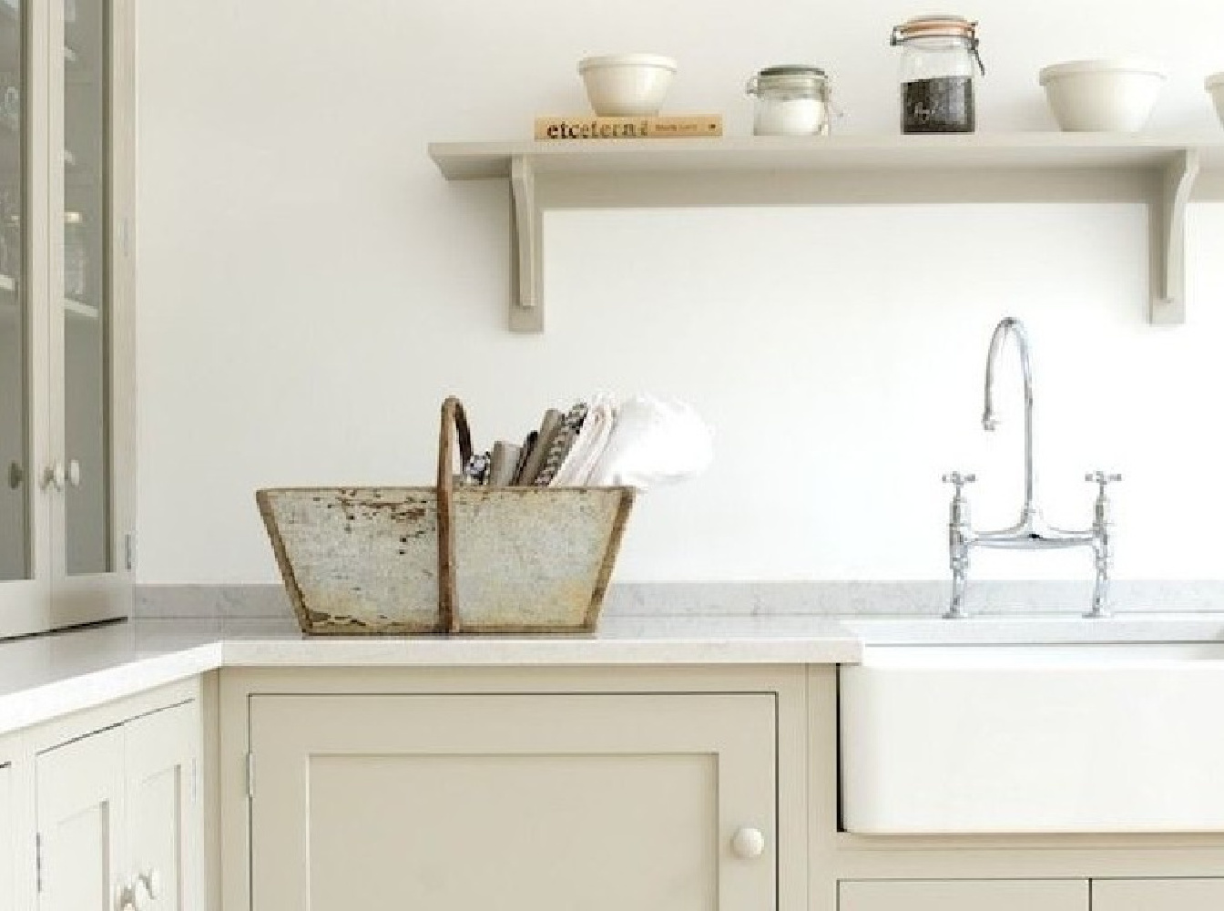 Gorgeous Shaker style kitchen by Devol with country style, Silestone Lagoon quartz counters, an open shelf, farm sink, and a chrome bridge faucet. #silestone #lagoon #quartz #kitchendesign