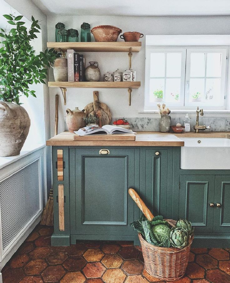 Charming rustic French farmhouse kitchen with green painted cabinets (Farrow & Ball Green Smoke), floating shelves, farm sink, and collected antique pots and baskets - Vivi et Margot. #frenchfarmhouse #rustickitchens #farmhousekitchen #greenkitchens #frenchcountry #kitcheninfrance #oldworldstyle