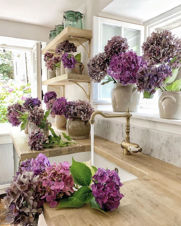 Lovely end of summer purple hydrangeas in a beautiful French farmhouse kitchen with wood countertops - Vivi et Margot. #frenchfarmhouse #frenchcountry #hydrangea #frenchkitchen #countrykitchens #woodcountertop #kitcheninfrance
