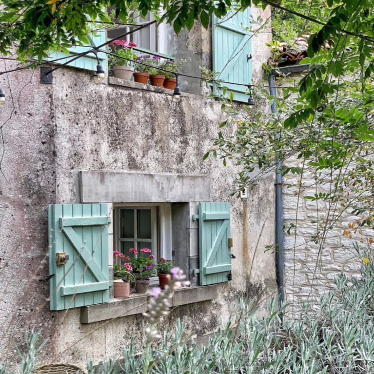 Rustic exterior of a French farmhouse near Bordeaux with green (Tollens) shutters and a darling window sill - Vivi et Margot. #frenchfarmhouse #exteriors #rusticcottage #frenchcottages #oldworldstyle #greenshutters #cottageinFrance
