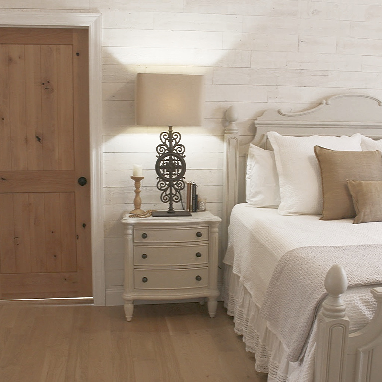 White French country cottage bedroom with Stikwood (hamptons) statement wall, white oak hardwood, and rustic alder doors. #hellolovelystudio #frenchcountry #bedroomdecor #rusticelegance #whiteoak #frenchbedrooms #alderdoor #stikwood #hamptons #romanticdecor #whitebedrooms #interiordesign