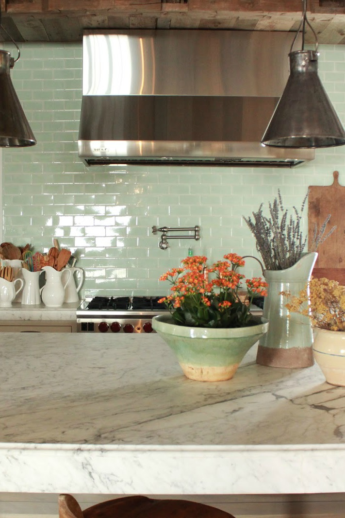 Green glazed subway tile in #FrenchCountry kitchen with stainless range hood #subwaytile