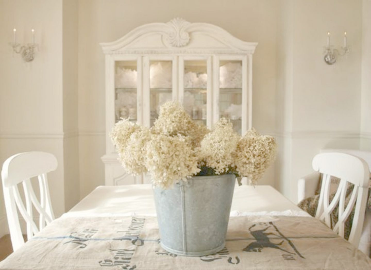 Hydrangea in bucket in French Nordic dining room by Hello Lovely Studio.