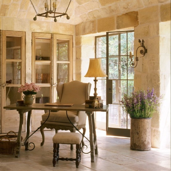 Breathtaking French country interior design in an office with reclaimed ancient limestone from France, lantern, linen, and rustic European antiques - Chateau Domingue. #frenchcountry #interiordesign #limestone #rusticdecor #frenchfarmhouse #chateaudomingue #frenchhouse