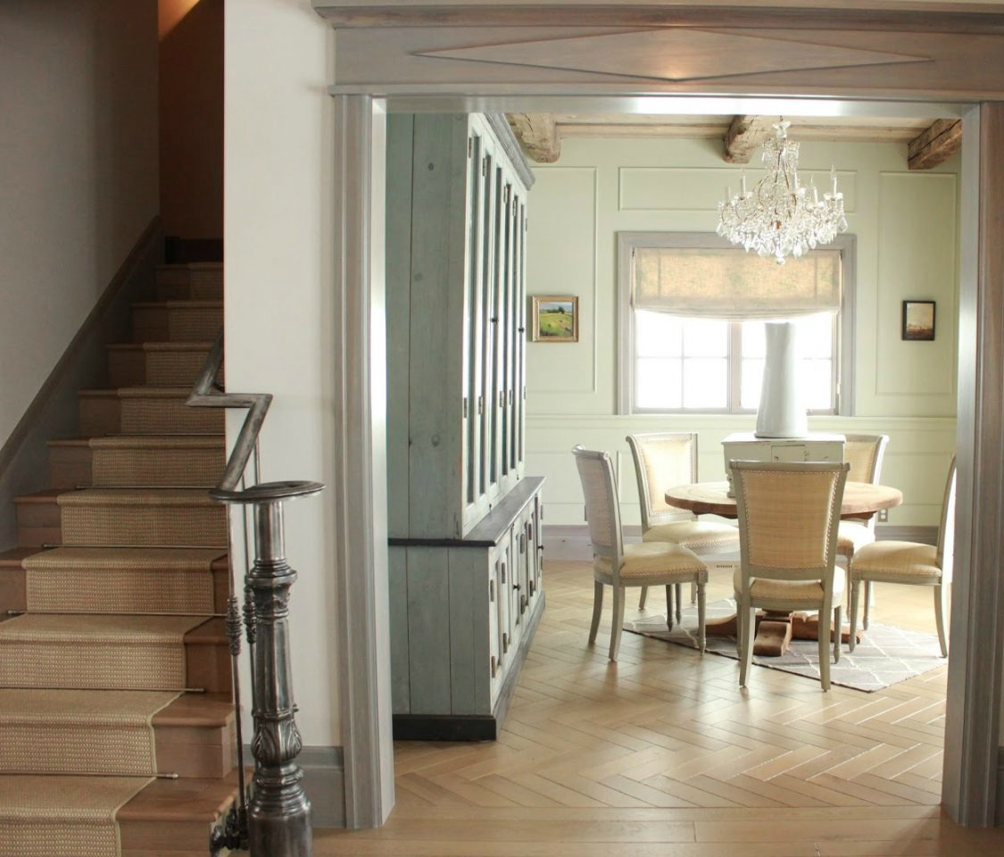 Entry and dining room with antique cabinet in French Country cottage on Hello Lovely