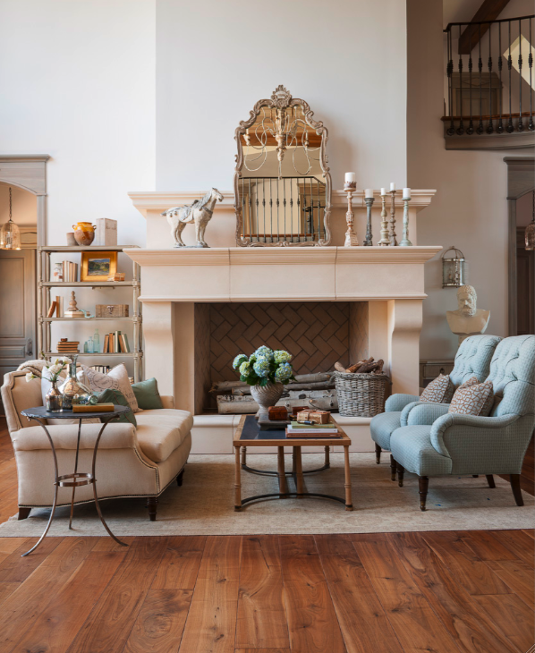 French limestone fireplace, rustic knotty wood floors, and a serene palette in this #FrenchCountry #livingroom by Decor de Provence. #limestonefireplace