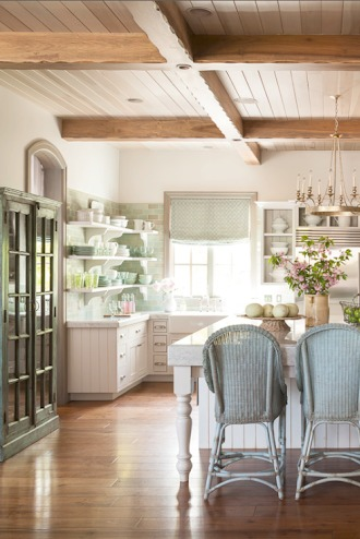 Natural light streams into a French Country kitchen with warm wood ceiling, white cabinetry, antique cabinet, open shelving, and aqua tile and accents. Decor de Provence. #FrenchCountry #Nordicdecor #Farmhousekitchen