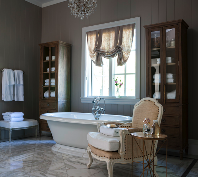 French Country cottage bathroom decor with freestanding tub, French chair, and glass fronted cabinets storing towels. Decor de Provence.