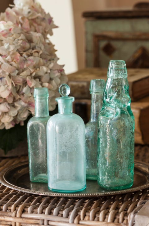 Green antique bottles in a French Country cottage on Hello Lovely Studio