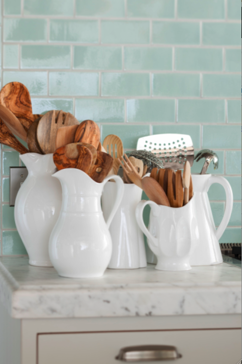 A collection of white pitchers hold wooden spoons and kitchen essentials in a French country cottage kitchen with glazed green tile. Decor de Provence.