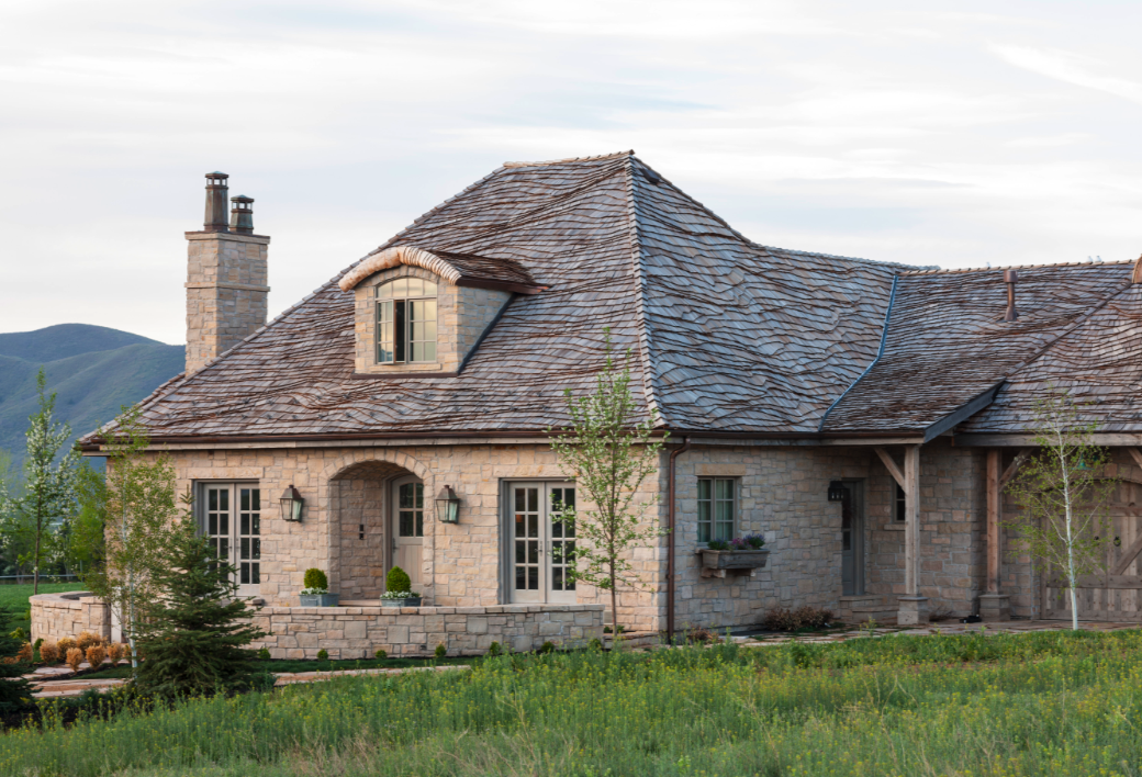French Country style home exterior with stone, slate roof, eyebrow architecture, and Gustavian details. #frenchcountry #frenchcottage #frenchfarmhouse #exterior