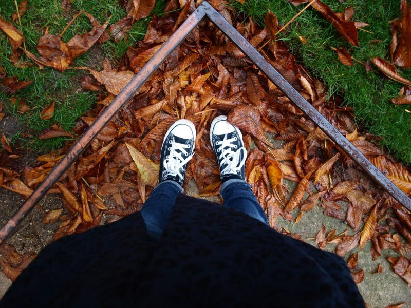 Black Converse in red fallen leaves in Paris