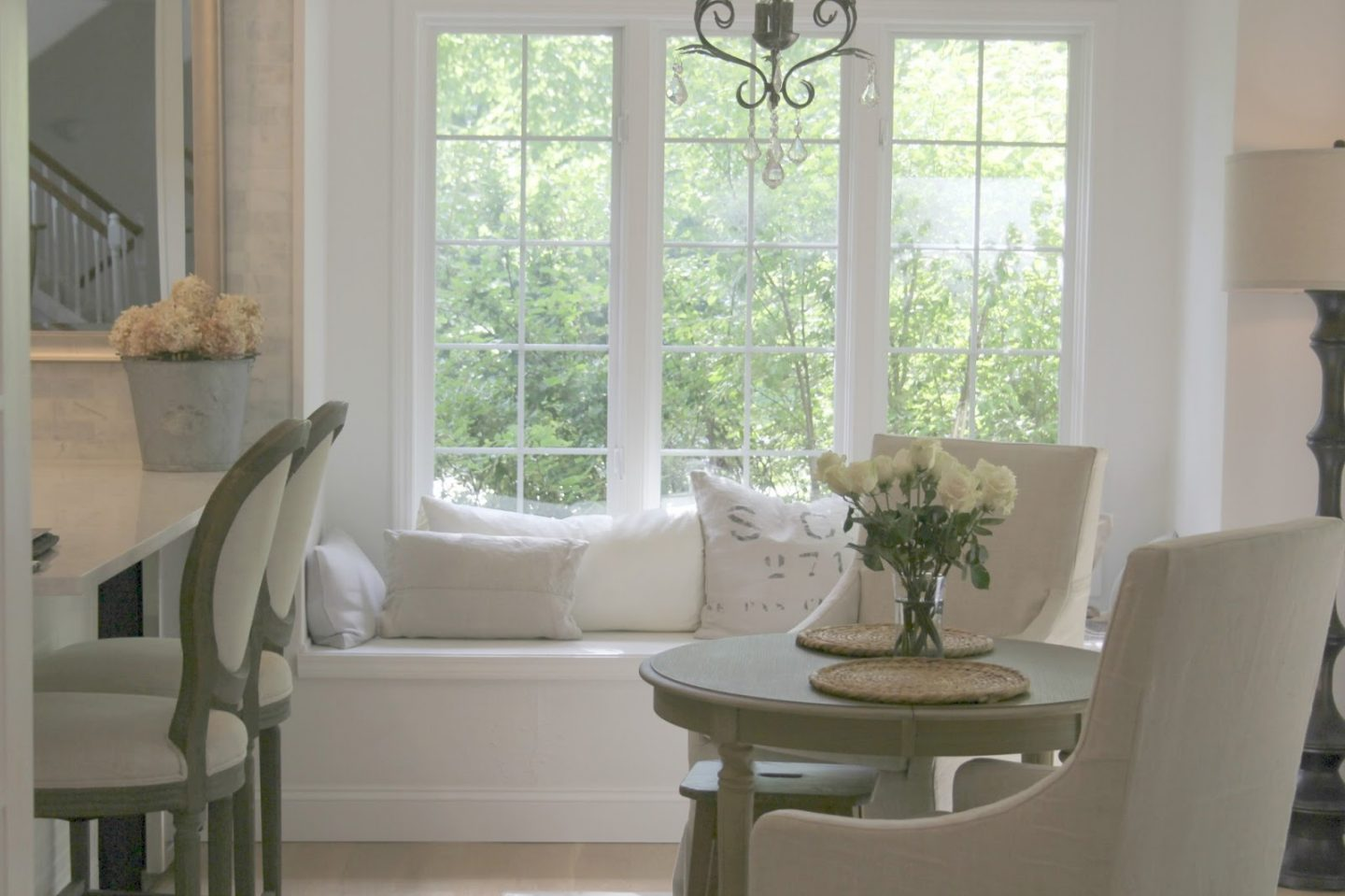 Serene whit kitchen with windowseat. Countertop is Viatera quartz in Minuet. Paint color is Benjamin Moore WHITE. Belgian linen French bar stools and slipcovered arm chairs with round wood dining table. #hellolovelystudio #kitchendecor #frenchcountry #serene #belgianlinen #europeancountry #neutral #windowseat #breakfastroom