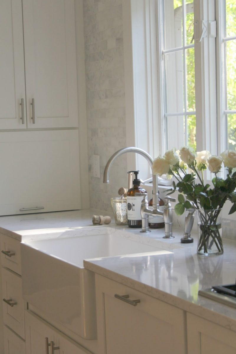 White Shaker style kitchen with apron front farm sink by Hello Lovely Studio