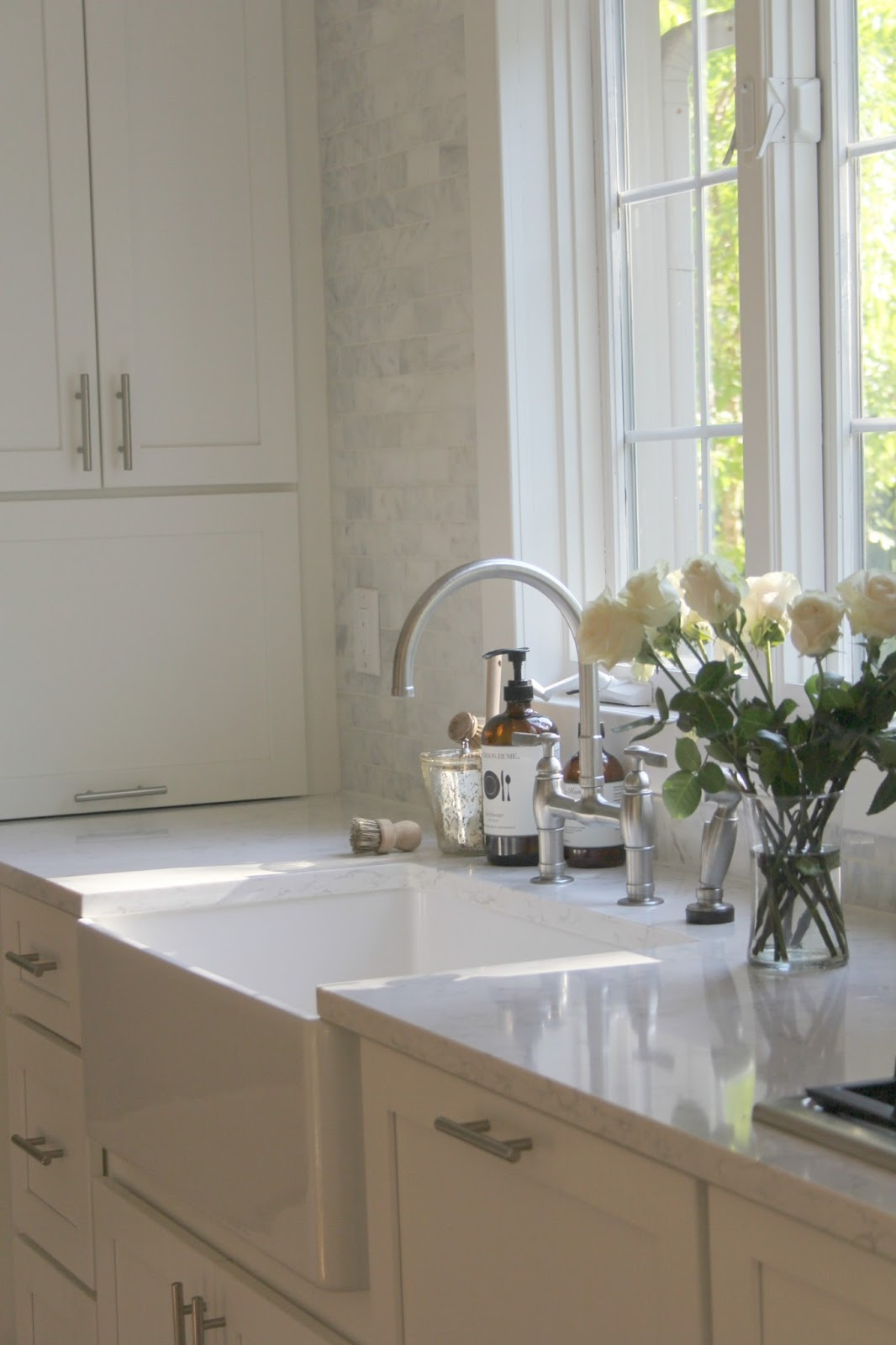 Modern farmhouse kitchen with white Shaker cabinets, farm sink, marble subway tiles, and white quartz counters. #farmsink #modernfarmhouse #kitchendecor #kitchendesign #whitekitchen #HelloLovelyStudio #minuet #quartz #serene #whitedecor