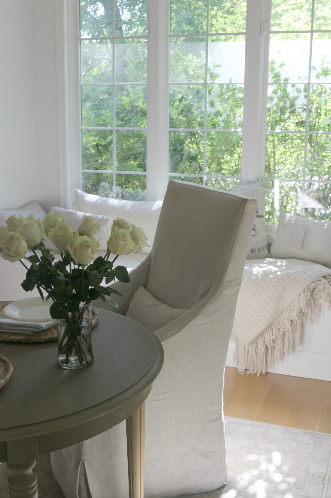 Window seat in white kitchen with dappled natural light, white roses, and European inspired decor. #hellolovelystudio #belgianlinen #windowseat