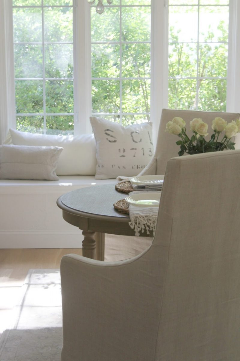Belgian linen chairs and window seat in calm white kitchen by Hello Lovely Studio