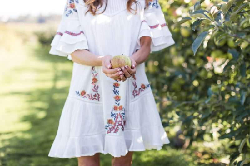 Leslie of Pretty Petals in boho dress holding apple