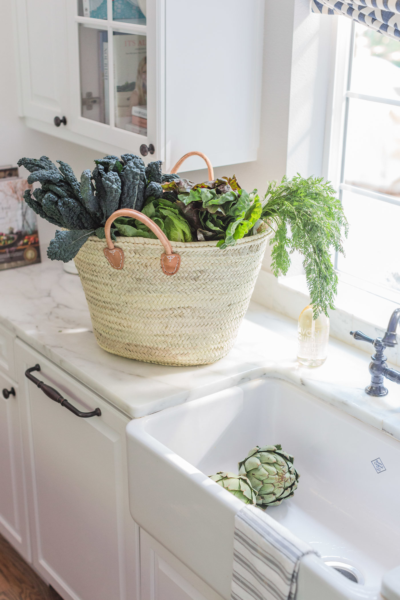 Beautiful white kitchen with market tote of farm fresh greens. Lemon Grove Lane.
