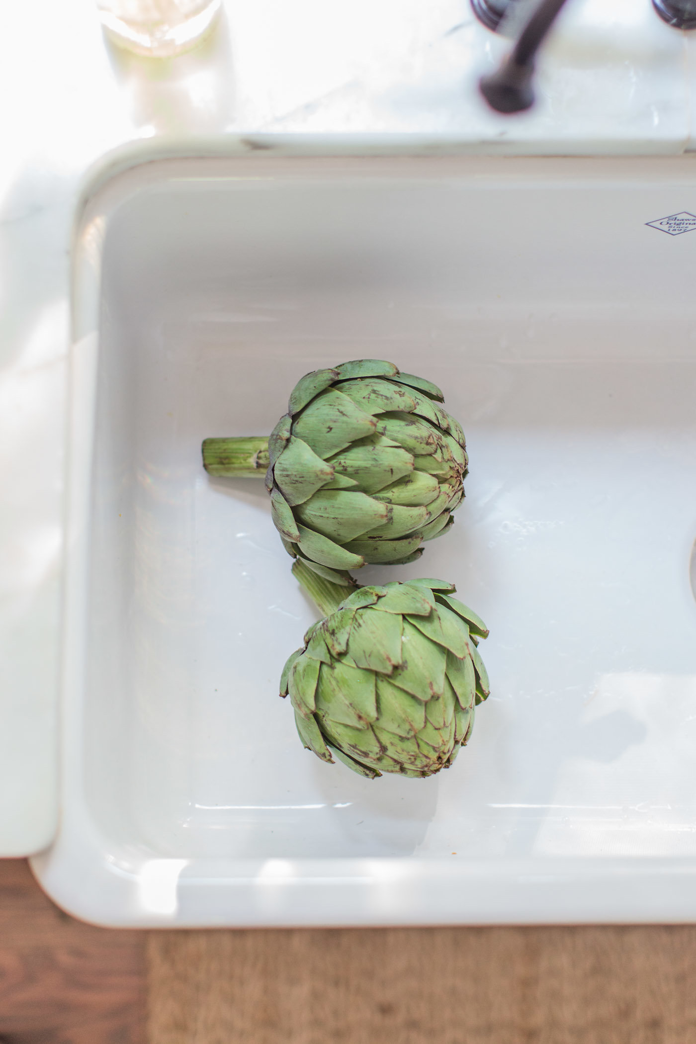 Beautiful artichokes in white farm sink by Lemon Grove Lane.