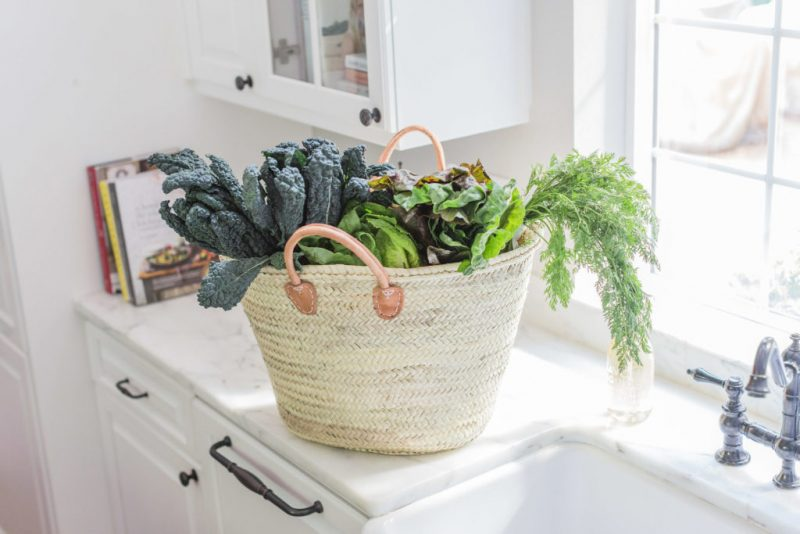 Gorgeous woven market tote with farm fresh greens and vegetables in white kitchen with marble