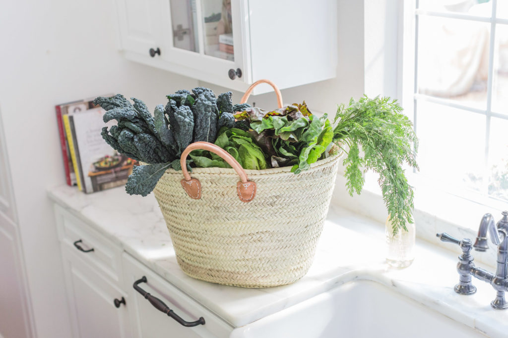 Gorgeous woven market tote with farm fresh greens and vegetables in white kitchen with marble. Lemon Grove Lane.