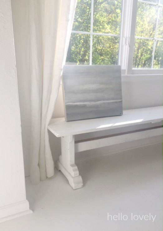 An abstract seascape by me rests on a reclaimed barn wood bench. White flooring and white linen curtains (RH). #hellolovelystudio #whitedecor #whitepaintedfloor #farmbench #abstractpainting #seascape #whitelinencurtains