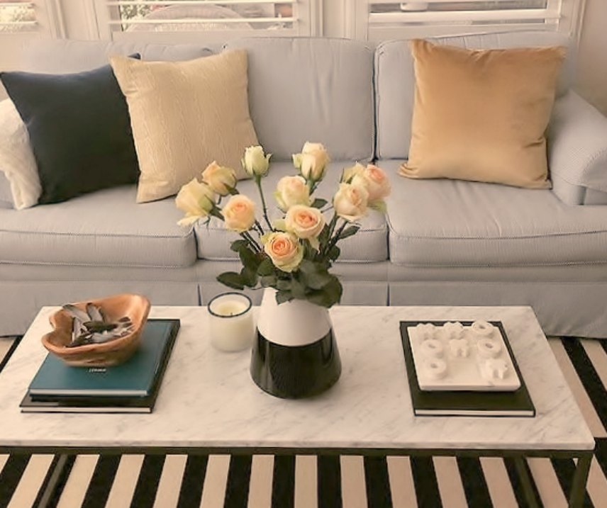 A classic living room with black and white stripe area rug and roses on the table - Good Life of Design.