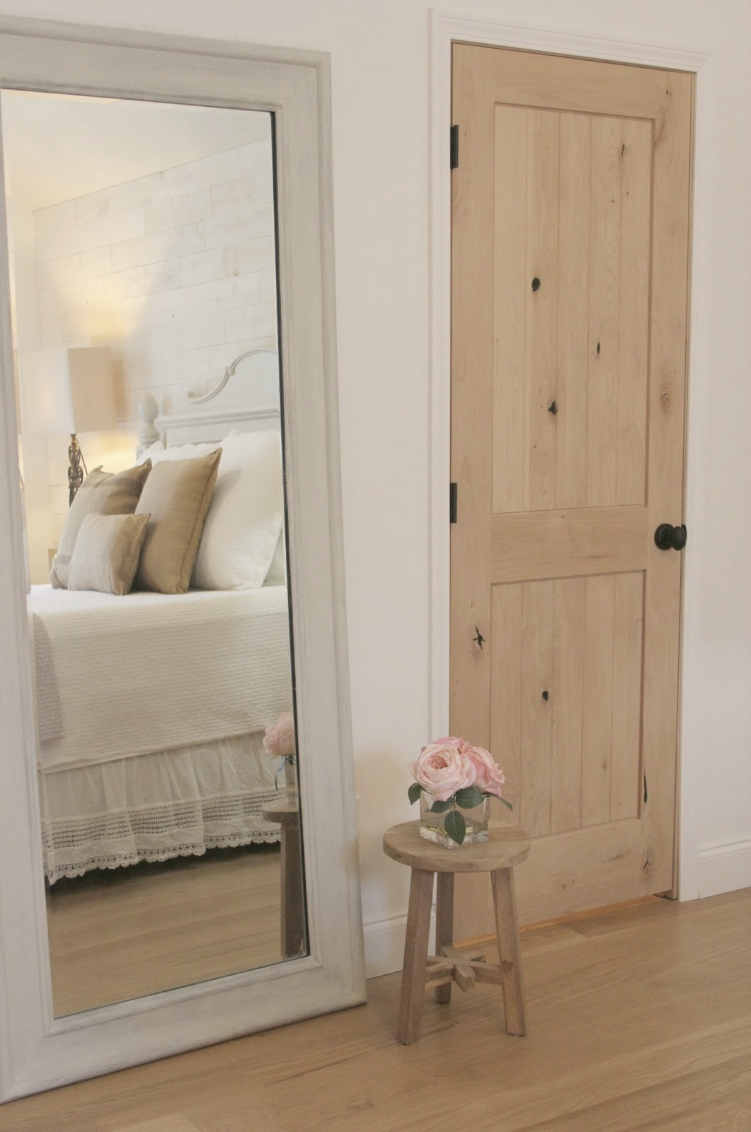 Romantic and white French country bed reflected in a leaner mirror in the bedroom. Foors are white oak hardwoods. White crochet lace bed skirt, Rustic three legged teak stool holds pink roses. Knotty alder closet door is full of character and oil rubbed bronze egg knob. Stikwood (Hamptons) reclaimed wood statement wall. #hellolovelystudio #bedroomdecor #stikwood #hamptons #knottyalder #alderdoor #whiteoakflooring