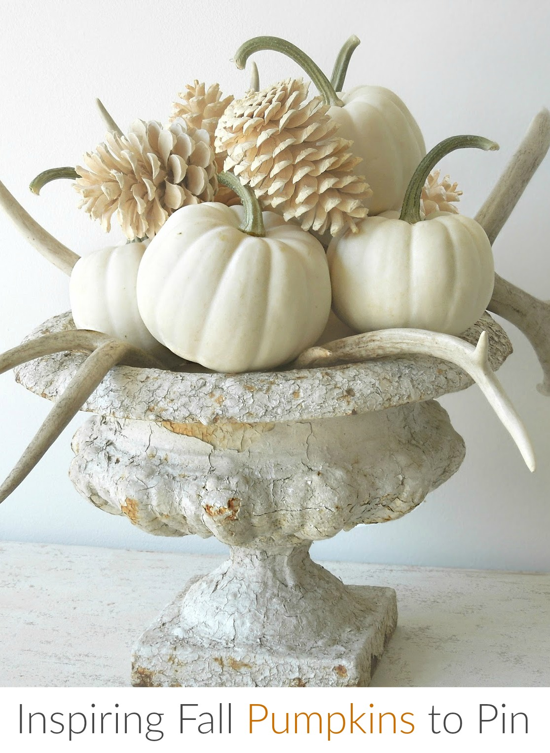 Tone on Tone white pumpkins and bleached pinecones in aged urn