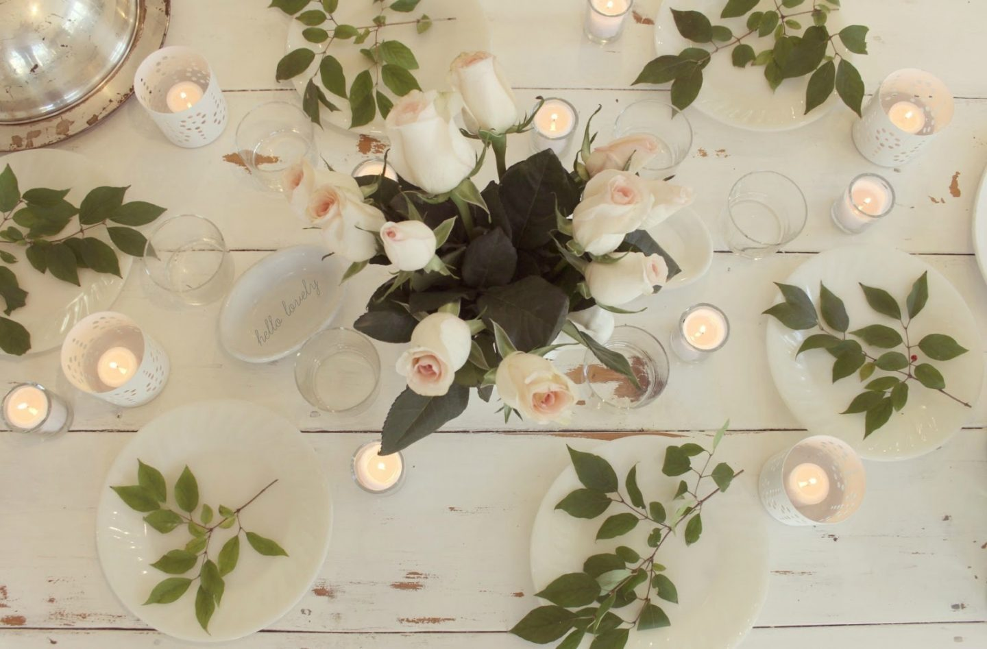 Candlelight, blush roses, and fresh greenery on a distressed white farm table with design by Hello Lovely Studio. #farmtable #farmhouse style #shabbychic #hellolovelystudio