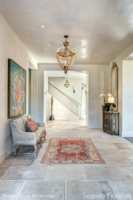 Exquisite entry in French Country home with plastered ceiling, French stone clooring, and French Country decor. Segreto Finishes.
