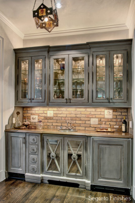 Gorgeous paint finish by Segreto to grey cabinets in a bar area with brick backsplash