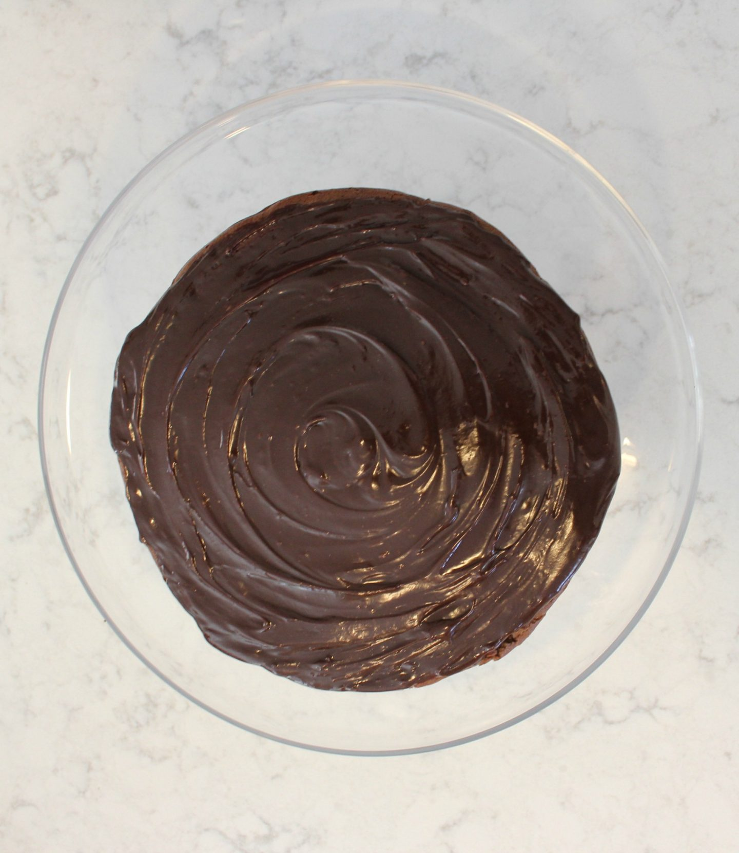 Round chocolate ganache iced cake on clear glass cake pedestal - Hello Lovely Studio