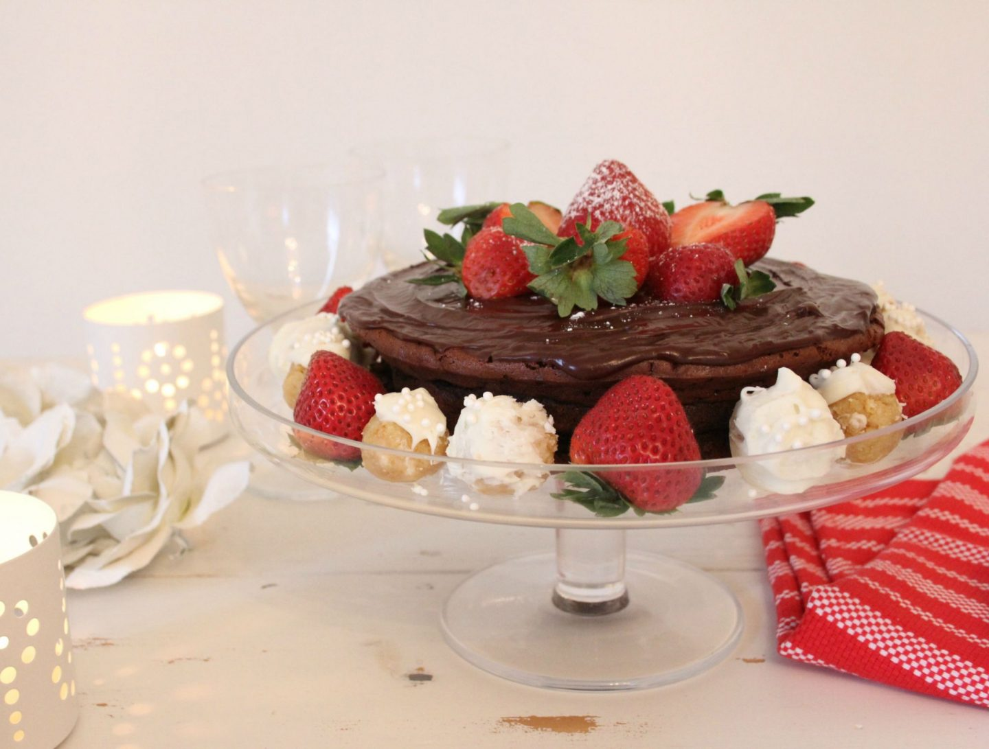 Beautiful gluten free chocolate cake decorated with berries and truffles - Hello Lovely Studio