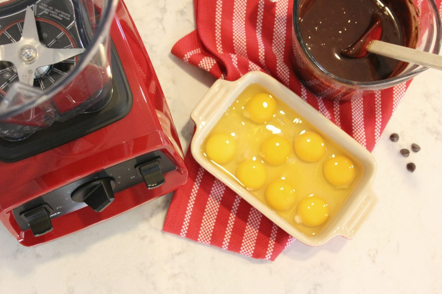 Red Vitamix Explorian E320 with eggs and chocolate on counter