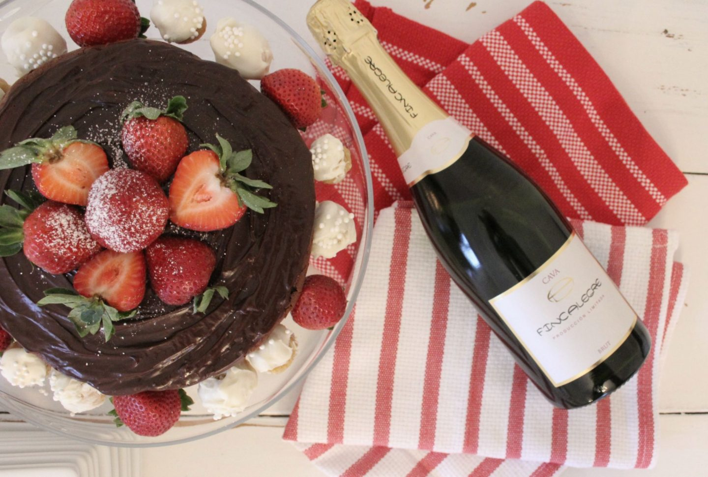 Beautiful chocolate cake, bottle of Cava, and red and white stripe dishtowels - Hello Lovely Studio