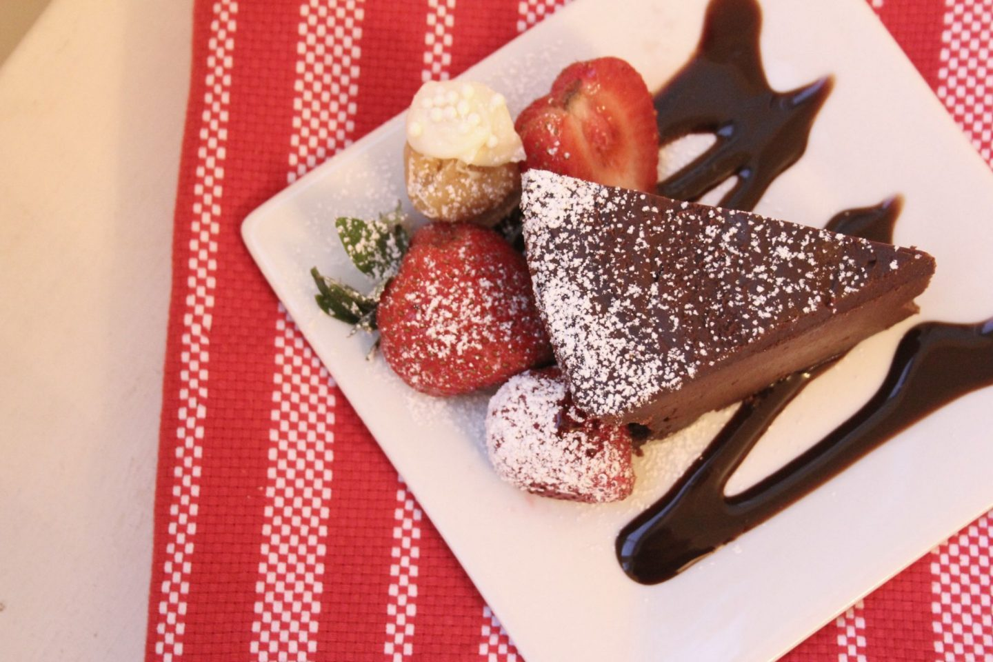 Slice of chocolate cake with strawberries and sugar cookie truffle