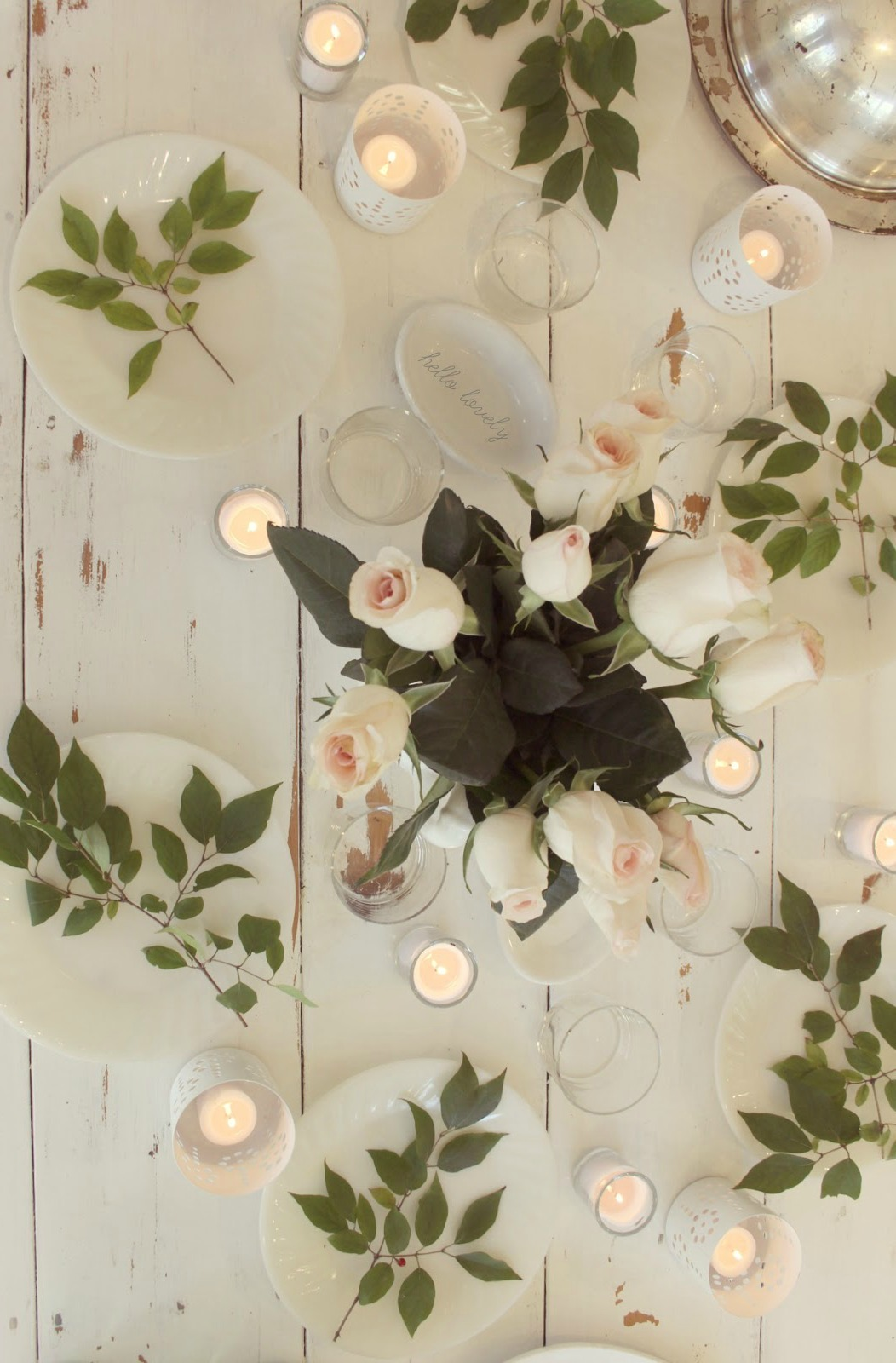 Pale pink roses upon a white farm table with serene, romantic tablescape - Hello Lovely Studio.