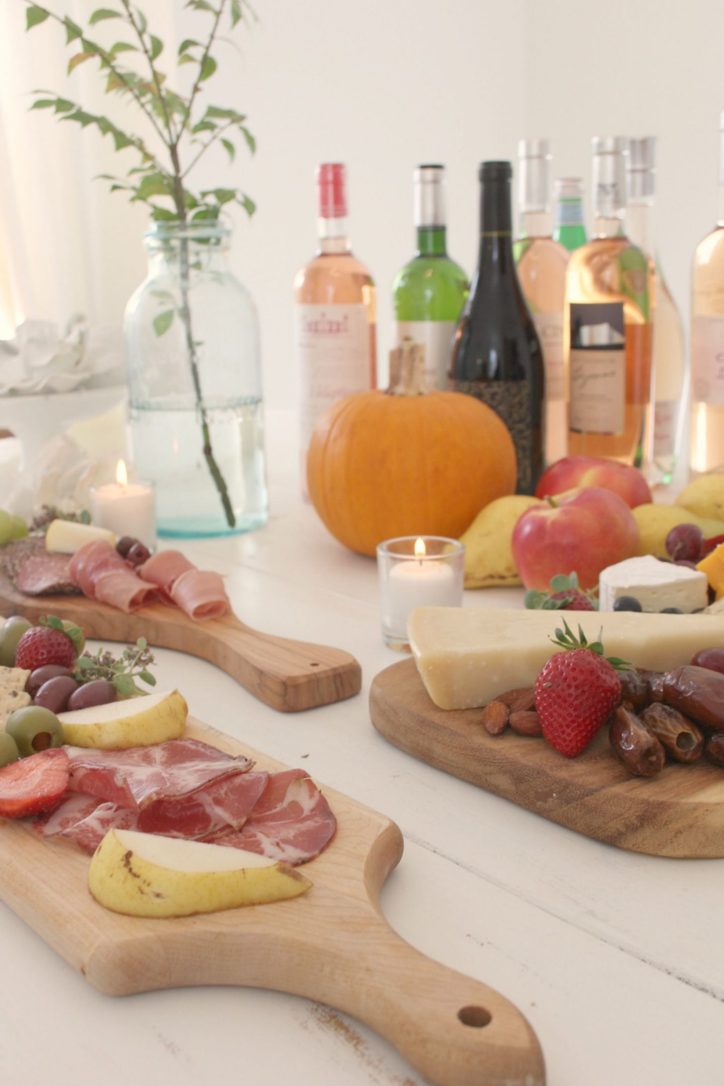 Beautiful cheese boards on white farmhouse table with wine