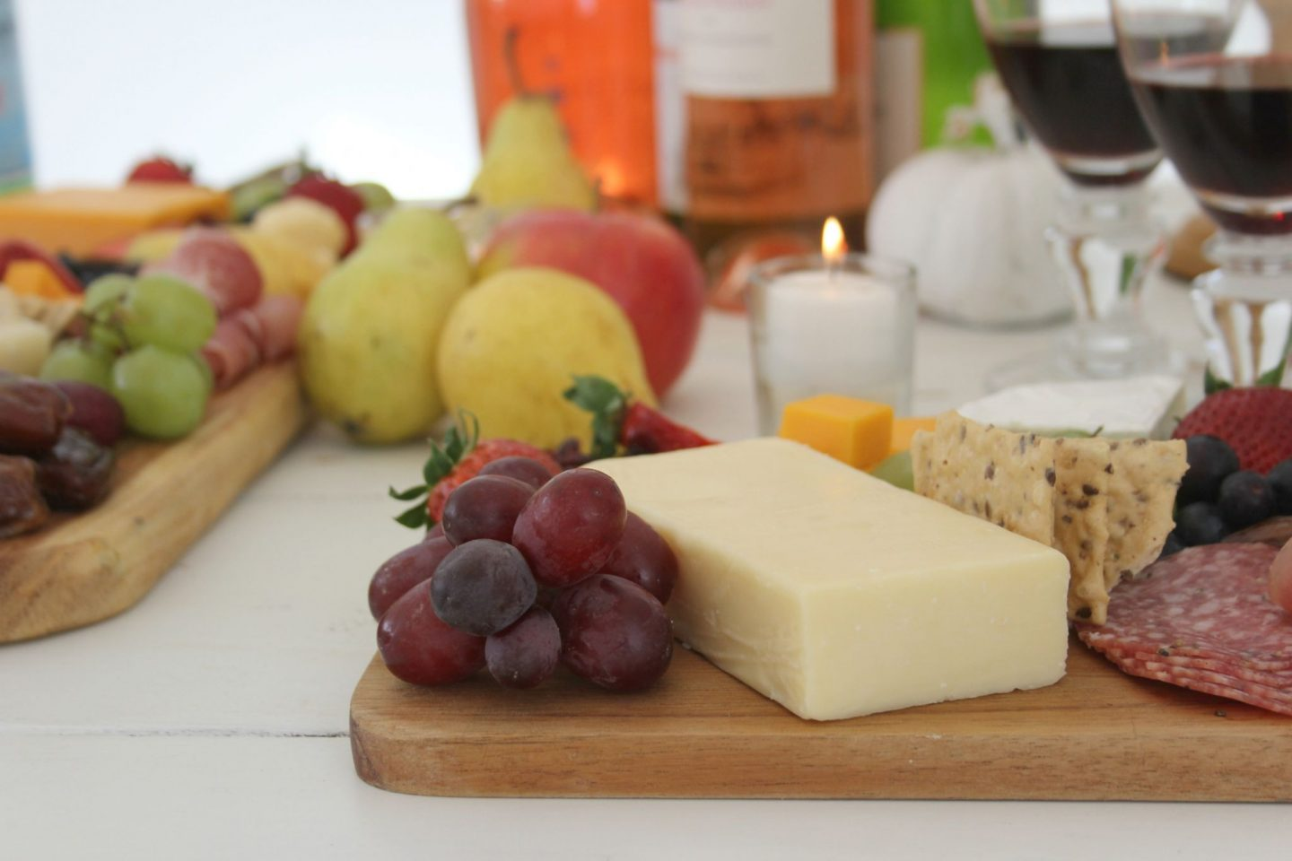 Cheese platters with fruit and candlelight on a white farmhouse table by Hello Lovely Studio