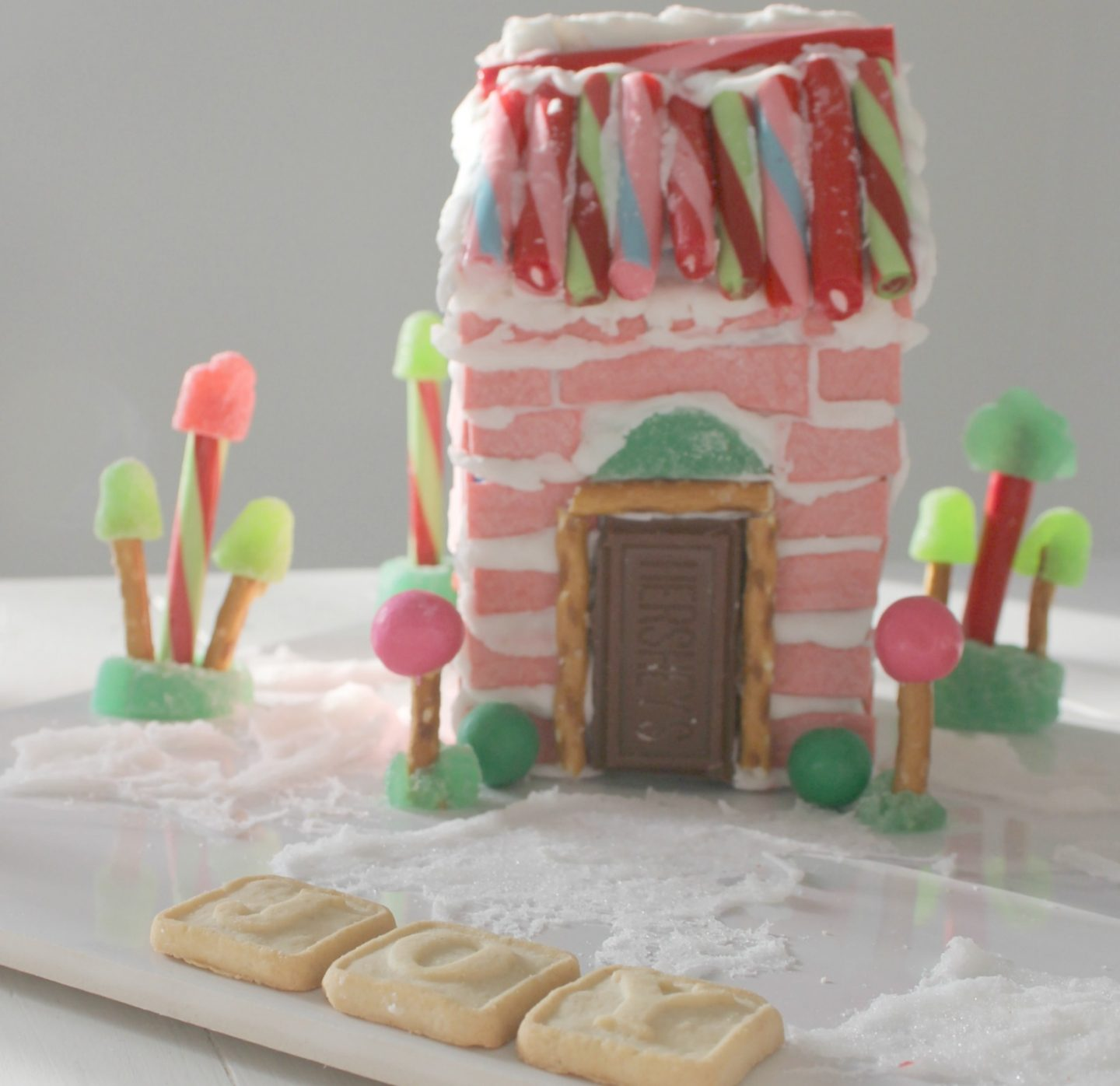Whimsical and festive homemade pink candy house made with sticks of gum - Hello Lovely Studio. CLICK OVER to find Christmas Decor DIY Ideas to Get Crafting for the Holidays Right Now as well as Decorating ideas! #christmasdecor #pinkchristmas