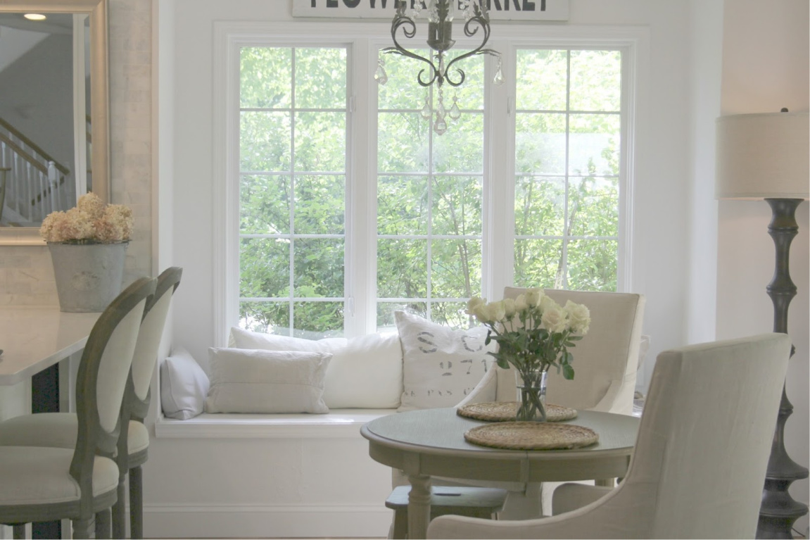 Serene white decor in breakfast nook with window seat and Belgian linen upholstery - Hello Lovely Studio. #kitchendecor #breakfastnook #windowseat #frenchfarmhouse #europeancountry #belgianlinen #frenchcountry #interiordesign