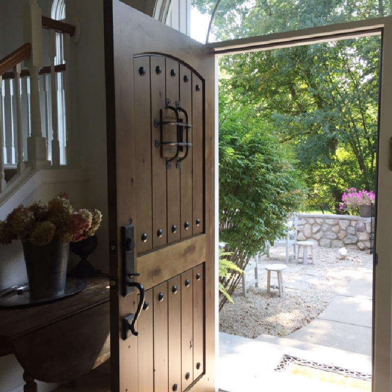 Knotty alder front door with speakeasy opens to a pea gravel French inspired courtyard - Hello Lovely Studio. #hellolovelystudio #entry #courtyard #frenchcountry #frenchfarmhouse #europeancountry #interiordesign