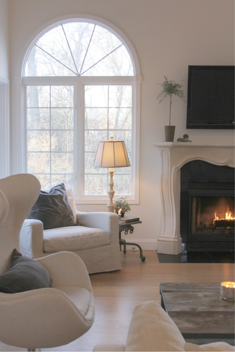Belgian linen upholstered chairs, white oak hardwood flooring, and a French fireplace in our European inspired country living room - Hello Lovely Studio.  You'll love these white paint color ideas!  #interiordesign #paintcolors