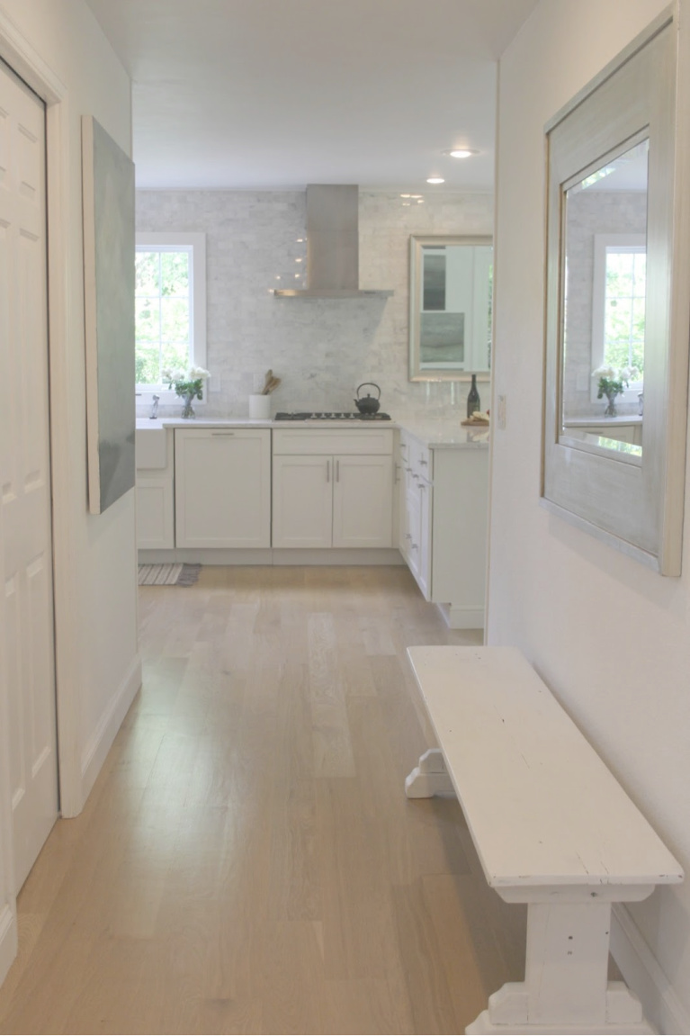 Hall to the kitchen has white oak hardwood flooring and is painted BM White - come find the just right white for your walls on Hello Lovely. #hellolovelystudio #interiordesign #whiteoakhardwood #benjaminmoorewhite #paintcolors