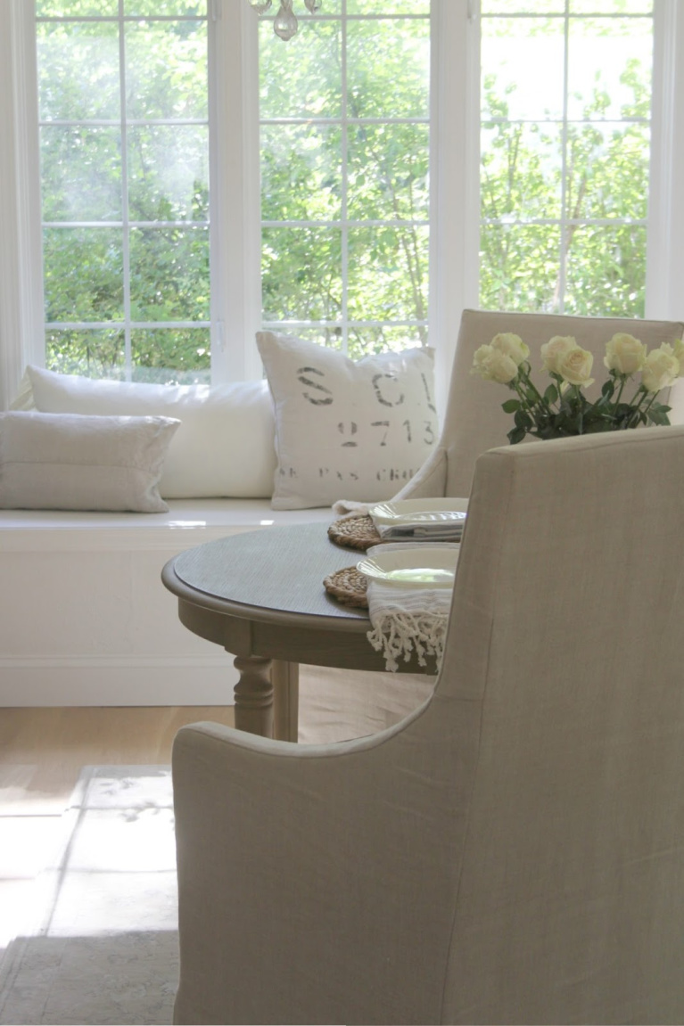 Serene white decor in breakfast nook with window seat and Belgian linen upholstery - Hello Lovely Studio. Our kitchen is BM White and you'll find plenty of smart suggestions for paint color here!