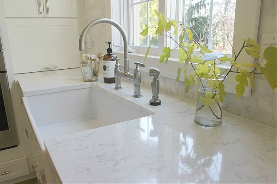 Viatera quartz countertop (Minuet) and fireclay farm sink in my serene white Shaker kitchen. #hellolovelystudio #viatera #whitequartz #minuet #quartzcontertop #farmsink #kitchendesign